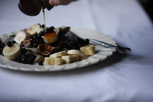 An image of maple syrup being poured on top of buckwheat pancakes topped with blueberries and bananas.