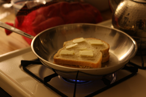 A small pan over a stove a piece of bread topped slices of cheese.