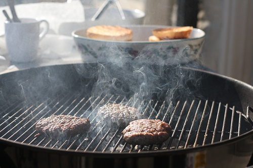 An image of a griller with smoke coming from it and burgers cooking.