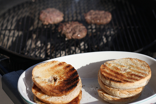 A close up image of grilled burger buns with burgers grilling at the back.