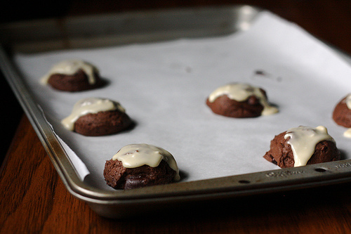 Chocolate cookies with frosting still in a baking tray.