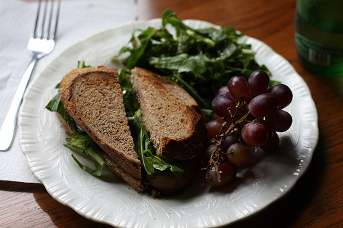 An image of a white plate, with a fork on a table napkin beside it, filled with a sliced sandwich on a bed of fresh greens and a bunch of grapes.