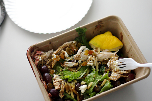 An image of s square bowl filled with delicious chicken and fresh green salad with a squeezed lemon in the corner.