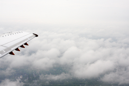 An aerial view of the clouds with a wingtip of a plane.