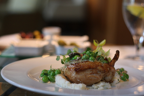 An image of a dish of split the drunken chicken topped with green peas.