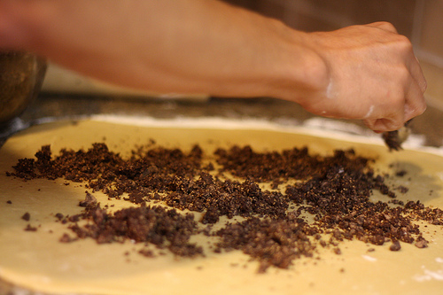 An image of a hand sprinkling chocolate over a flattened dough.