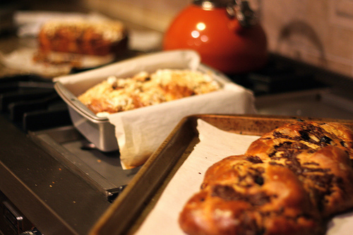 An image of a chocolate babka on a wooden with a few more bread pieces at the back in different containers.