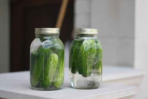 An image of two glass jars filled with pickles.
