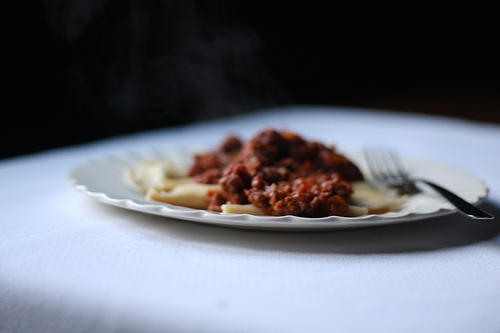 A plate of ravioli topped with meaty sauce.