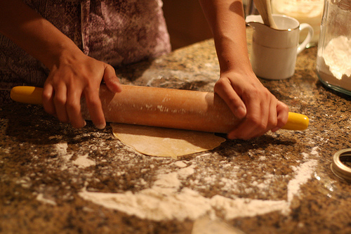 An image of a woman holding a rolling pin over a piece of dough on a kitchen table smeared with flour.