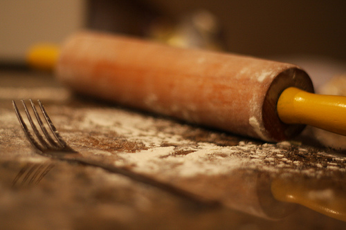 A close up image of a rolling a and a fork on top of a table smears of flour on top of it.