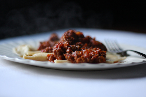 A close up image of a white plate filled with ravioli topped with meaty sauce.