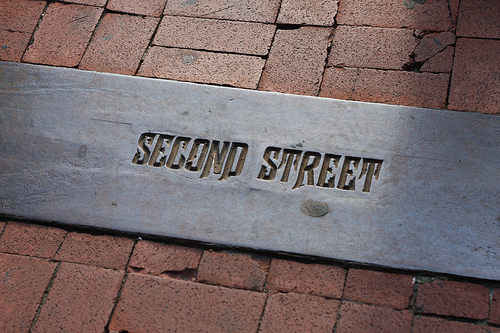 An image of a name of a street etched on the brick pavement.