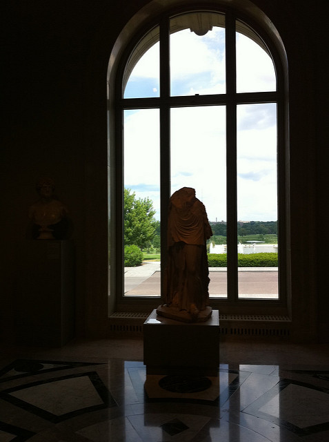 A silhouette of a statue against an arched window.
