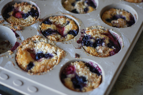 An image of a baking muffin tray filled with cooked berry muffins ready for eating.