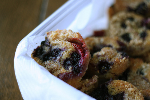 An image of a white container with delicious berry muffins.