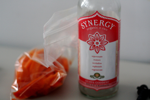 An image of a bottle labeled Synergy and a ziplock plastic beside it filled with orange stuff.