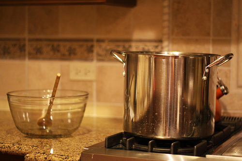 An image of a kitchen counter with a large steel pot and glass bowl with stirrer.