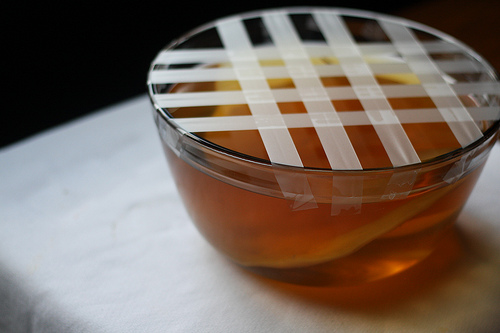An image of a glass bowl with crisscross tape over the edge.
