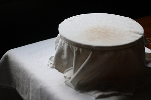 An image of a glass bowl covered with clean white cloth.