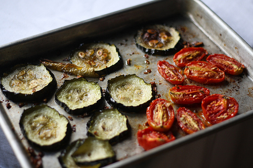 An image of roasted tomatoes and zucchini slices on a baking tray.