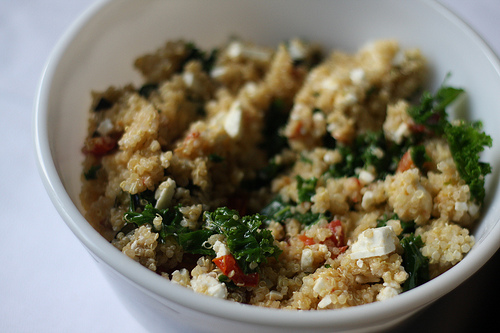 An image of a bowl of quinoa, zucchini, tomatoes and cheese.