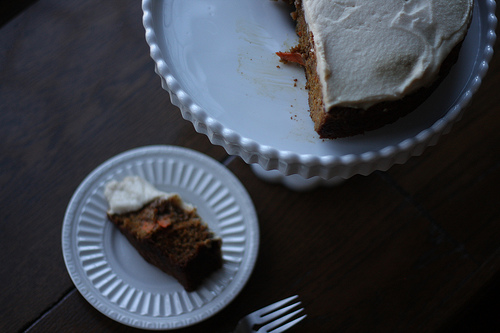 A top view of a carrot cake with frosting on a cake stand and a slice of it on a plate.