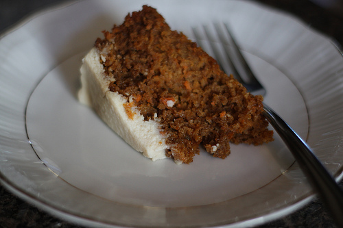 A close up image a slice of a carrot cake with frosting on a white plate a fork beside it.