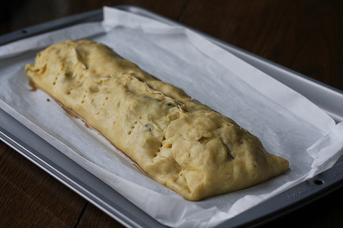 An image of an uncooked apple strudel ready to go into the oven.