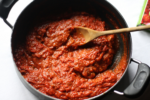 A top view image of a pot filled with red sauce and wooden in it for stirring,