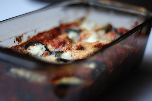 An image of a baking dish with eggplant slices, cheese, and red sauce.