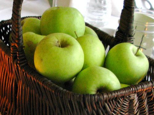 An image of a crisp green apples inside a woven basket.