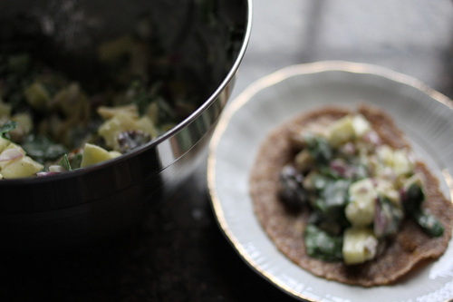 An image of a tin bowl with salad mixture in it and a white plate with a tortilla and salad.