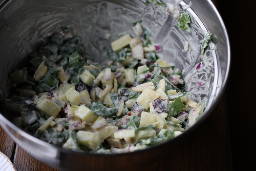 A top view image of a tin bowl filled with waldorf salad mixture.
