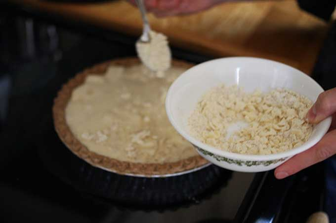 Adding ingredients on top of the pie to form a streusel topping | Foodal