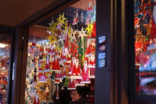 An image of a store window showing various hanging Christmas ornaments.