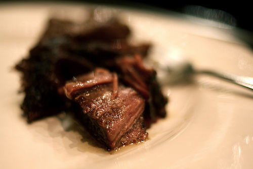 A close up image of soft juicy pot roast on a white plate.