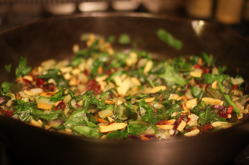 Colorful herbs and spices being sauteed in a pan.
