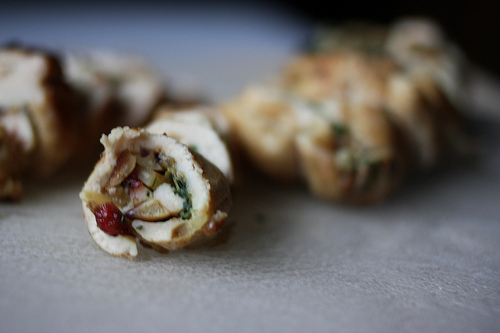 A close up image of flavorful chicken roulade sliced into bite sizes.