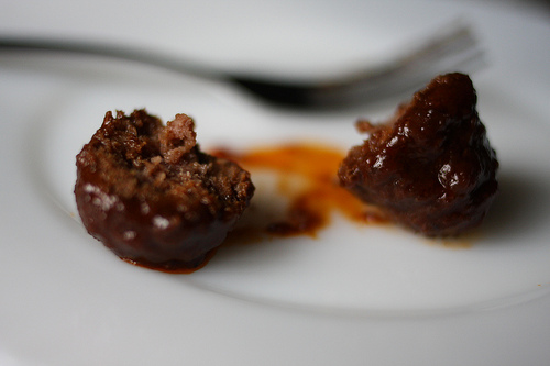 A close up image of a meatball, sliced in half.
