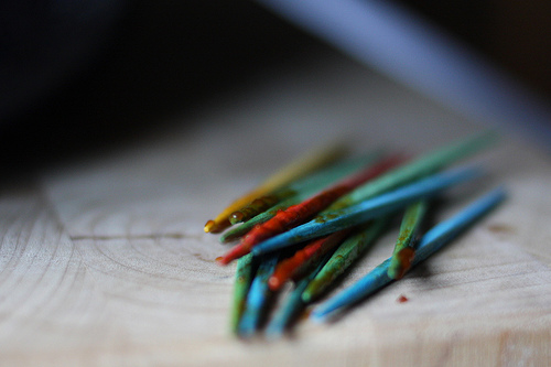 An image of colorful toothpicks on a wooden slab.