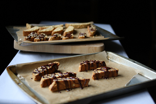 An image of two trays filled with anise biscotti with chocolate topping.