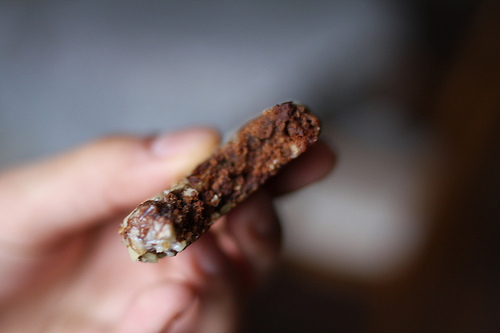 A half-eaten chocolate cookie being held by a hand of a woman.