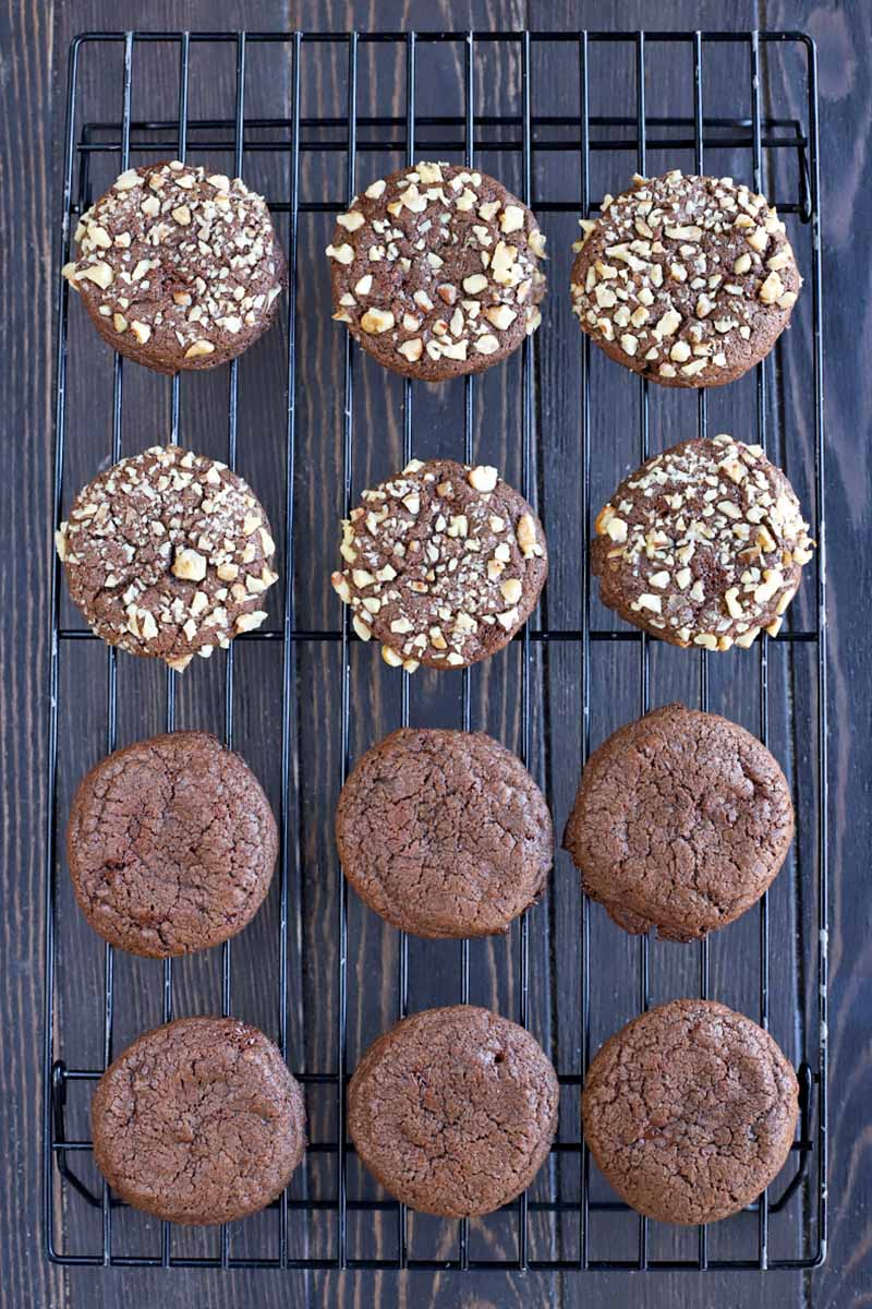 Overhead vertical shot of plain and walnut-coated chocolate cookies arranged in four rows of three on a black metal cooling rack, on a dark brown wood surface.