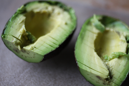 A close up image of a halved ripe avocado with its pit removed.