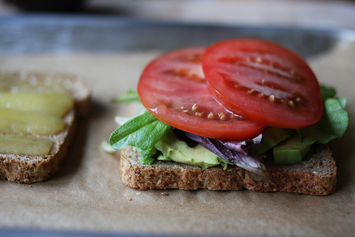 An image of a bread with tomato slices, mixed greens, and mashed avocado.