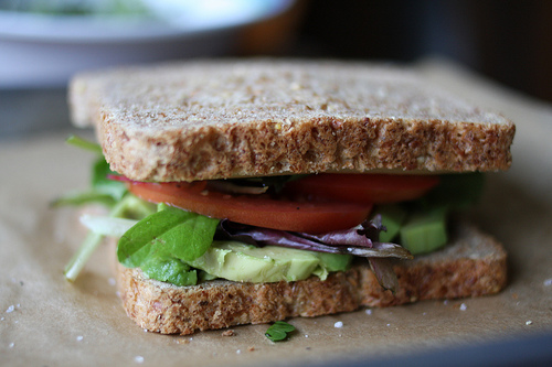 A beautifully made sandwich filled with tomatoes, mixed greens, avocado, and cheese.