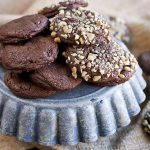 Walnut and plain chocolate truffle cookies on a blue ceramic cake stand, with more of the baked goods scattered on a gathered piece of burlap.