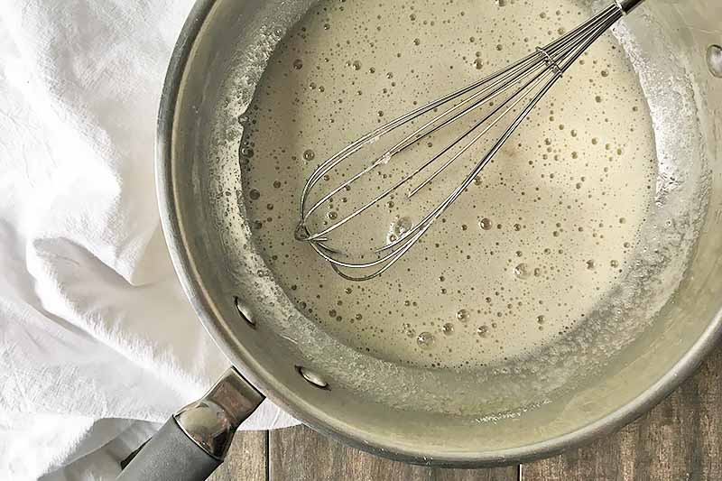 Horizontal image of a frothy white mixture and a whisk in a metal pan.