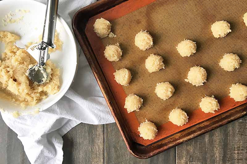 Horizontal image of portioning dough on a baking sheet pan lined with a silicone mat.